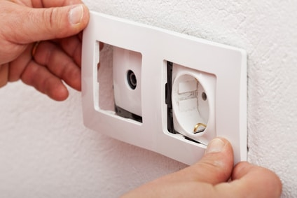Male electrician hands changing an electical wall outlet or socket - closeup